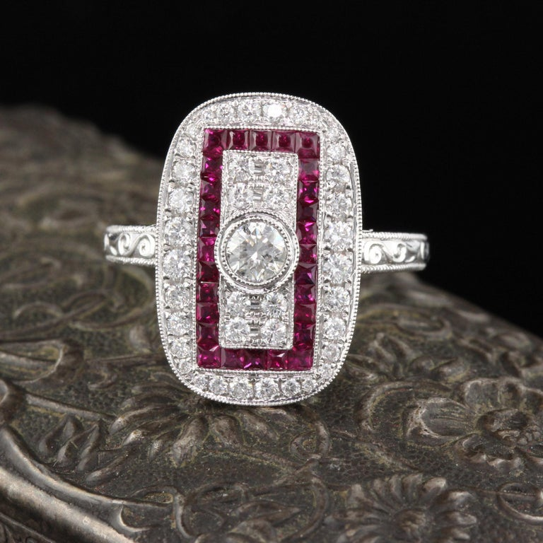Beautiful Art Deco style ring in 18K White Gold with diamonds and channel set natural rubies! This ring is hand engraved and mil-grained.  Item #R0057  Metal: 18K White Gold  Center Diamond Weight: 0.25 cts   Total Diamond Weight: 0.76 cts  Diamond