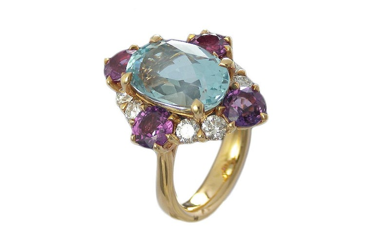 This  Art-deco looking, statement 5.88 carat oval cut Aquamarine  framed in a 4 claw and surrounded  by 3.10 carat Round Pink Sapphires and 0.91 carat Round Diamonds all prong set in 18 Karat Pink Gold.   Ring Details:   Aquamarine : 5.88
