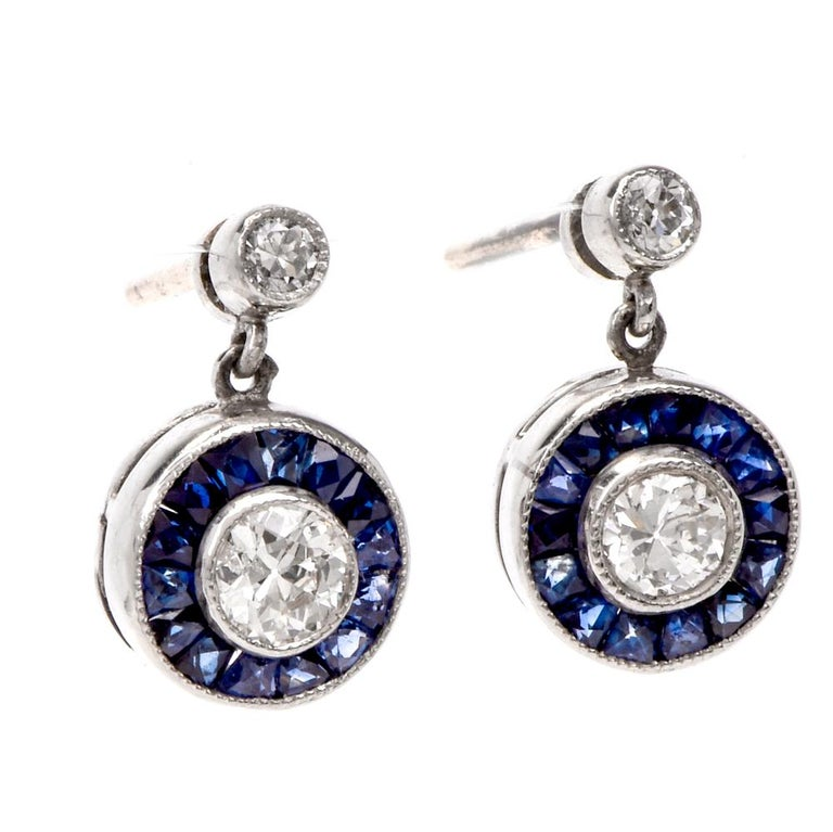 These estate art deco style circle diamond and sapphire dangle stud earrings are crafted in solid platinum. Displaying two stud round-cut diamonds and two center diamonds collectively weighing approx. 0.45cts, H-I color, SI clarity. Surrounded by a