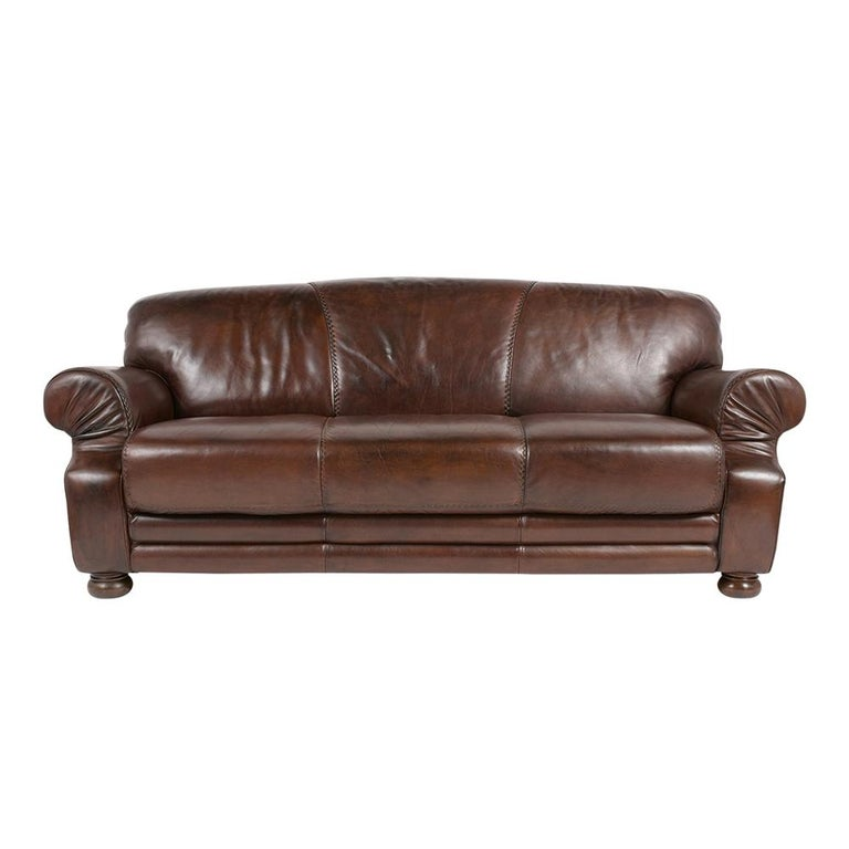 This Vintage Leather Club Sofa is in great condition and has been dyed in a dark brown color with a patina finish. This sofa features three attached seat and back cushions, and comfortable armrests with cross-stitch/ single piping details on the