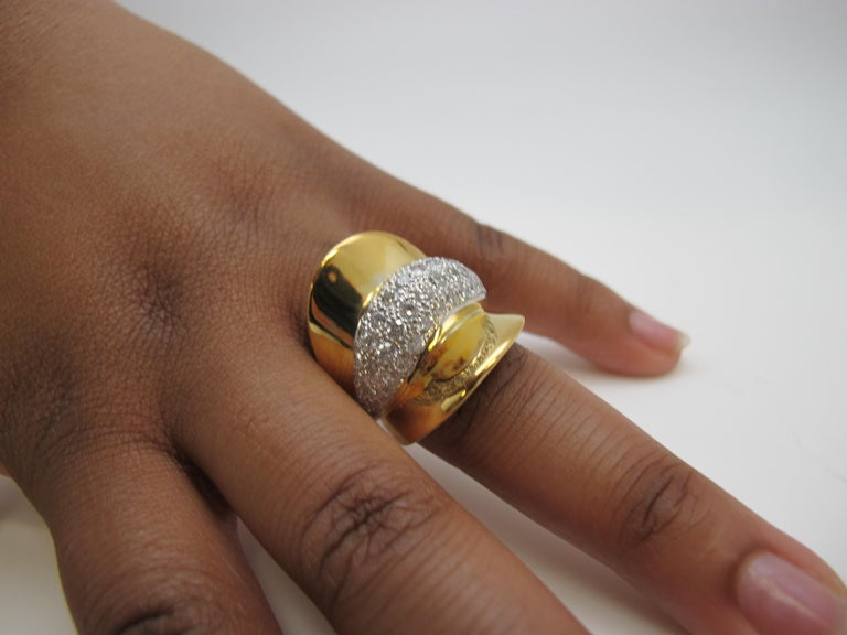 Big and bold best describes this ring! Although a contemporary piece, one could argue the design is  inspired by either the Art Deco movement or that it has a '50's Retro vibe. It is made of 18k yellow gold which is highly polished and set with 50