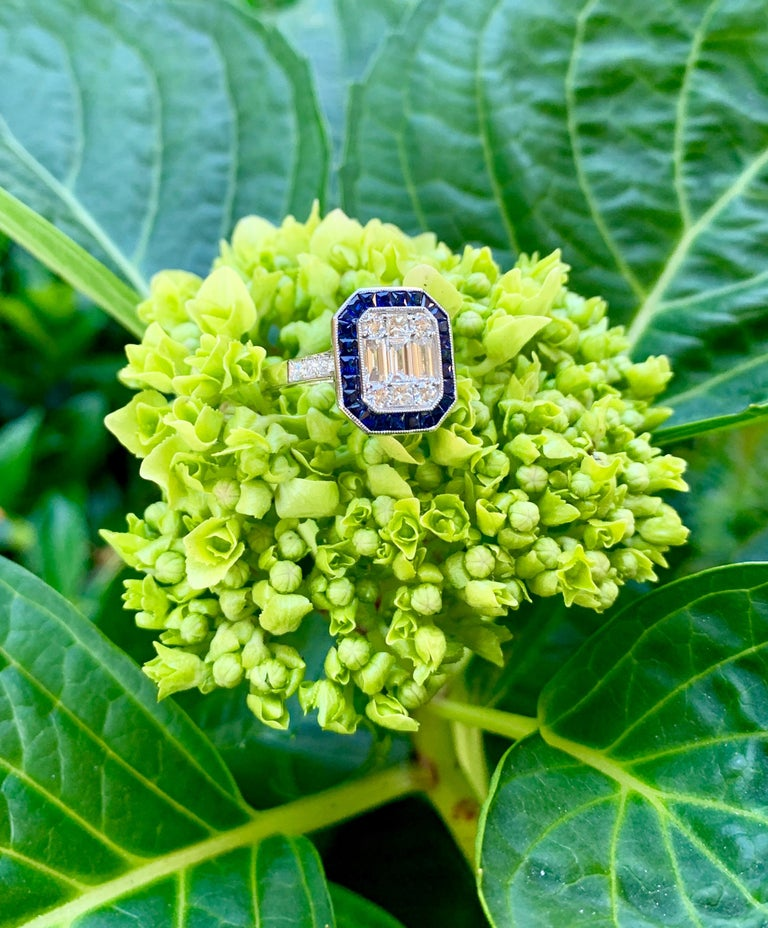 Beautiful Art Deco style ring features invisibly set baguette and shared prong set round diamonds giving the illusion of a very large, cut corner rectangular step cut diamond in the center. The center diamonds are surrounded by a contrasting halo of