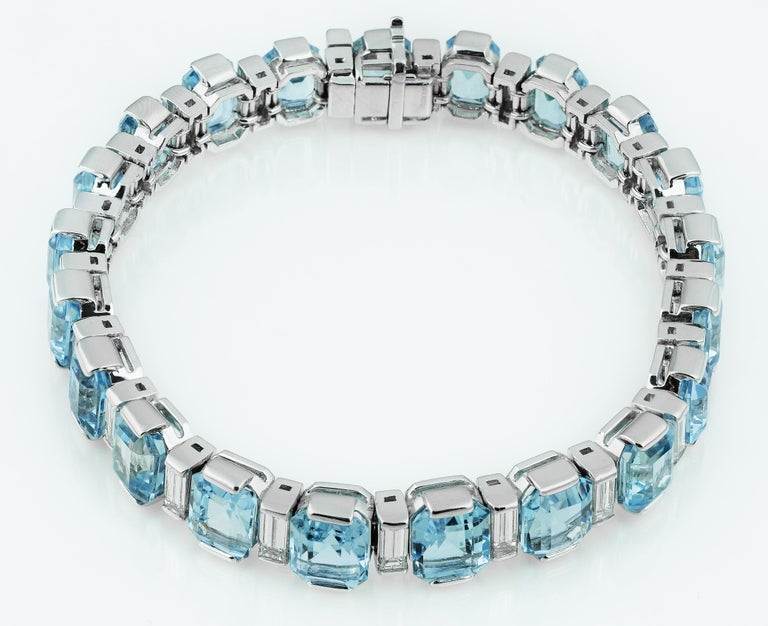 Stunning aquamarine and diamond bracelet with hidden box clasp. Alternating emerald cut clear sky blue colour aquamarine and baguette cut diamonds set in platinum.  21 x Aquamarine approximate total weight 34.0 carats 21 x Baguette cut diamond,