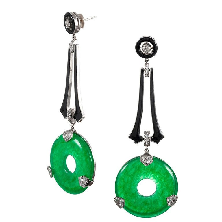 Dropping 2 7/8 inches from the ear, these glamourous art deco style earrings combine polished rings of apple green jade with brilliant white diamonds and the drama of black enamel. They are rendered in platinum and set with .50 carats of antique cut
