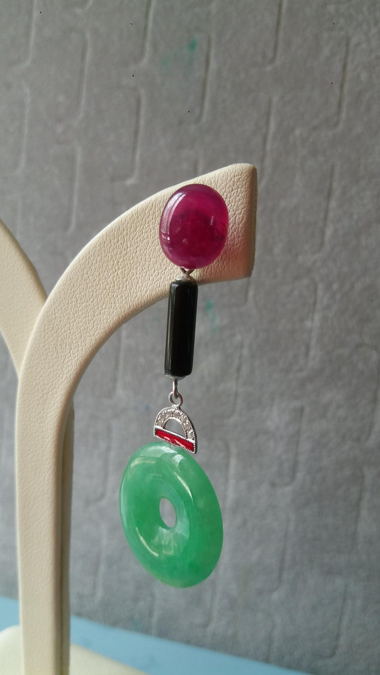 These earrings have in the upper part 2 large ruby cabochons, the central part consisting of 2 cylinders of black onyx and 2 elements in gold diamond and red enamel, while in the lower part we have 2 jade discs In 1978 our workshop started in Italy