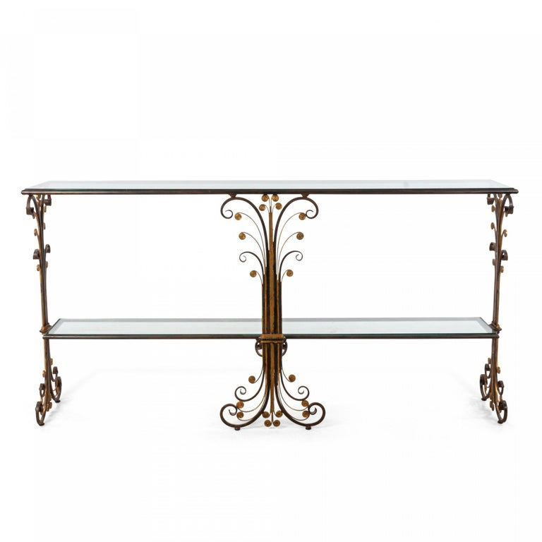 French Art Deco style two-tier iron console (Davenport) table with gilt trim and scroll design sides and center support with an inset glass top and shelf.
