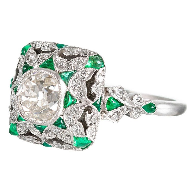 The design of this ring is inspired by the distinctive creations from the Art Deco period, yet the piece is of newer manufacture. Hand made in platinum, the centerpiece is an old mine cut diamond that weighs 1.12 carats that exhibits natural color