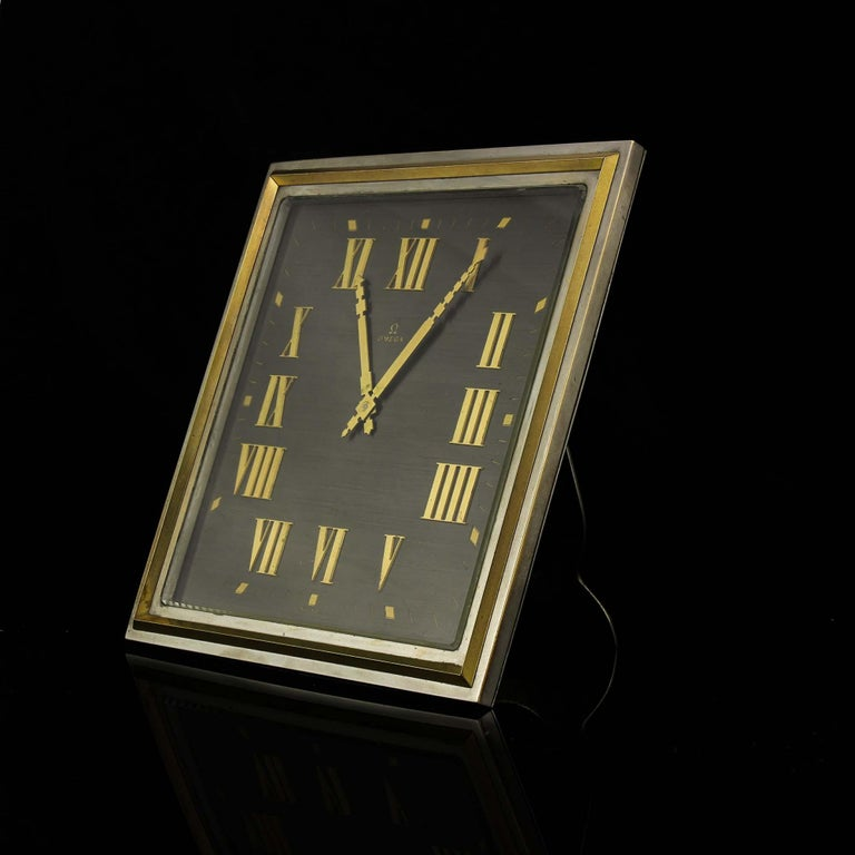 Art Deco style Omega silver plate table/desk clock with 8 day movement and Roman numerals.  Object: Table clock Material: Plated brass Clock mechanism: Mechanical Power reserve: 8 day movement Striking: Not striking Estimated period: