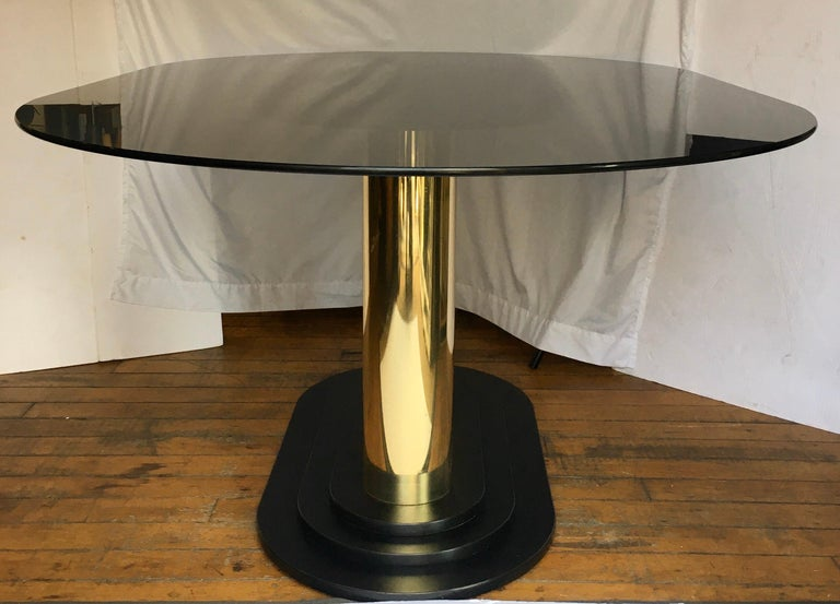 Art Deco style oval dining table featuring a removable smoked glass oval top and a reflective gold double column pedestal base. This modern sculptural piece would also make a stylish center table. Coordinating brass dining chairs also available for
