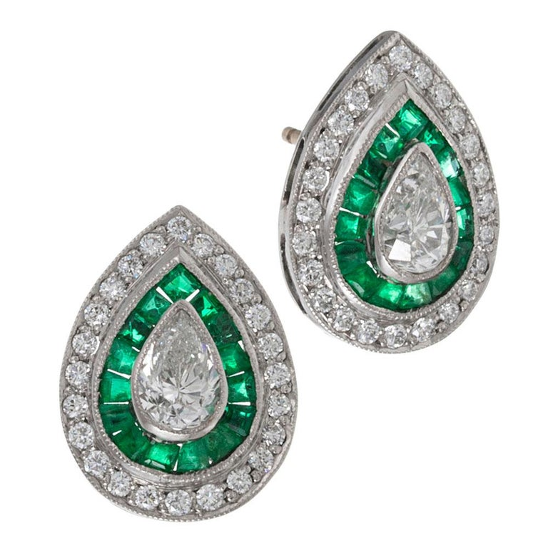 These teardrop-shaped ear studs centered upon a pair of pear brilliant white diamonds, framed in a rippling halo of emeralds and brilliant diamonds are handmade in classic art deco tradition, yet are of more modern manufacture, offering spectacular