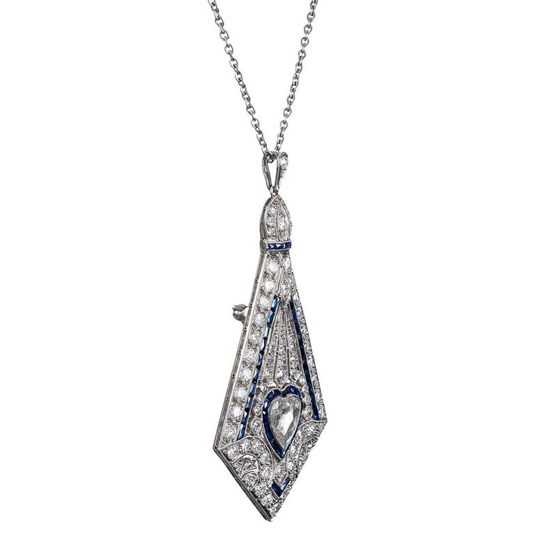 Exquisitely crafted to embody the meticulous creations of the art deco era, this handmade platinum pin/pendant is a celebration of intricate craftsmanship and masterful skill. The piece measures an impressive 2.5 inches long and 1.25 inches wide,