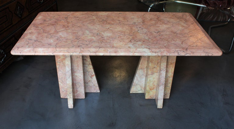 Elegant Art Deco style pink marble low table consisting in a rectangular top with two geometric bases, Italy, 1930s.