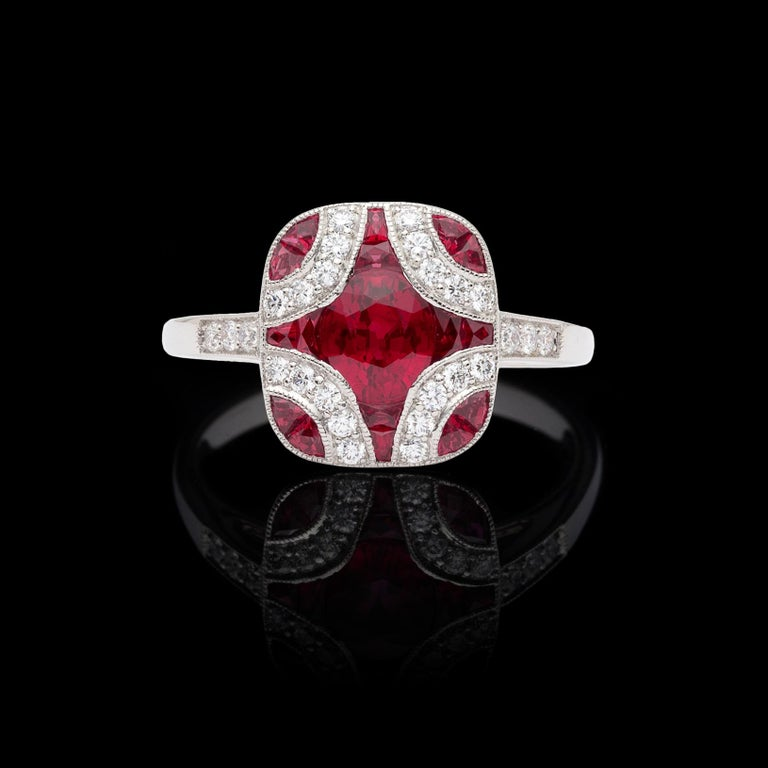 Art deco design and beautifully crafted, this platinum ring is reminiscent of an earlier era. Set with oval and calibre-cut rubies totaling 1.20 carats, and highlighted with sparkling round brilliant-cut diamonds, the ring is eye-catching and