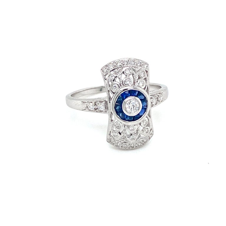 Beautiful Gold handmade Art Deco style ring. It is set in 14k white Gold featuring a sparkling Round brilliant cut diamond in the center, surrounded by an halo of custom cut natural Sapphire, all embellished by Round brilliant cut diamonds G/H color