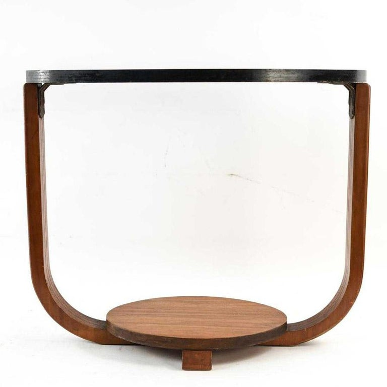 The Art Deco style side table has at the bottom an oval wood display shelf, fluted wood supports and a black lacquered oval top. Could also be used as a small coffee table.