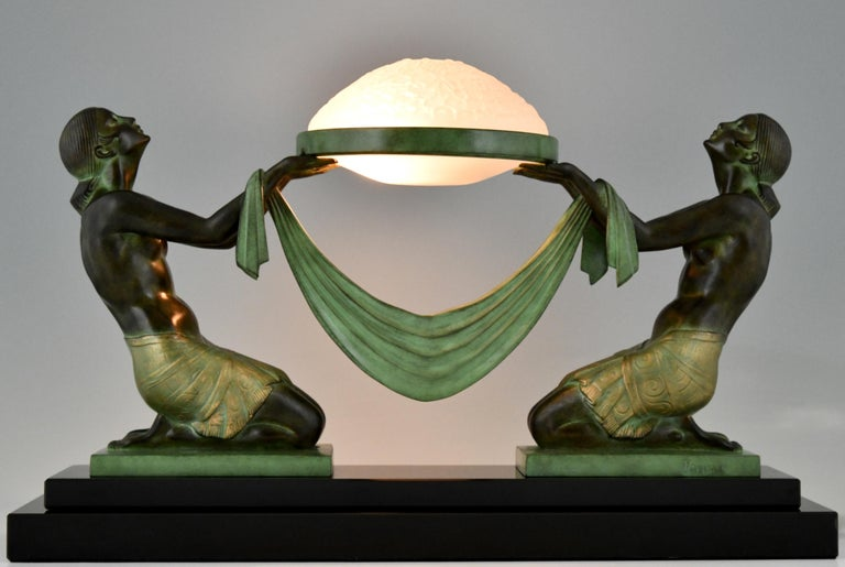 Offrande ?Art Deco table lamp with kneeling nudes holding a glass shade.  By ?Fayral, pseudonym of Pierre Le Faguays.  Design Ca. 1930.? Posthumous contemporary cast at the Le Verrier foundry.  Patinated Art metal. ?Glass shade. ?Black marble