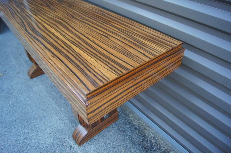 This striking console, in a richly grained zebrawood, has a muscular Art Deco aesthetic. The top is 4.5 inches thick with a slight setback along the front and sides. An aluminum bar stabilizes the 3-inch-thick legs, which curve inward and back out