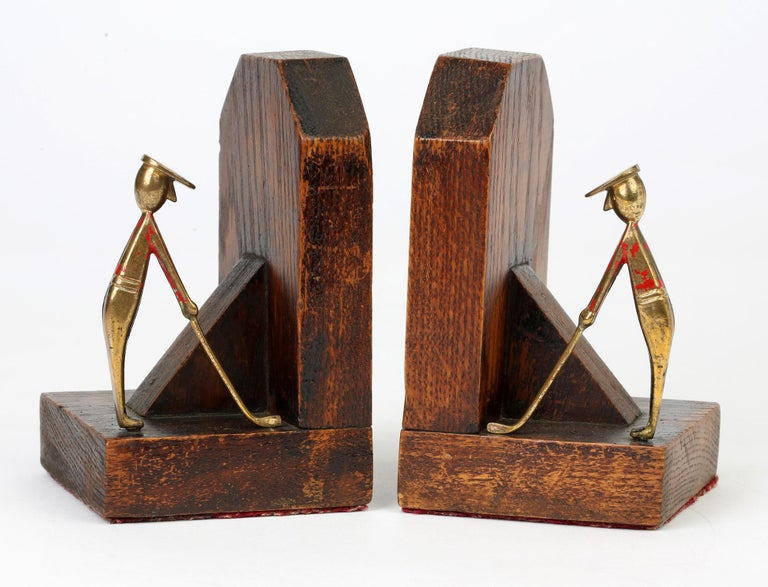 Stylish pair Art Deco stained wooden bookends mounted with enameled brass golfing figures dating from circa 1925. These stylish bookends are made up of two carved blocks of wood joined by an angled central strut and each with a Hagenauer style brass