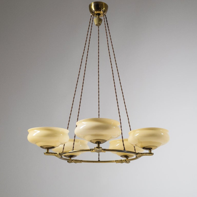 Rare Art Deco suspension chandelier, from the 1930s. Brass ring with five cast brass arms, each with a blown glass diffuser. The glasses are triple layered with sand tinted glass on the in- and outside and a white central layer for an overall cream