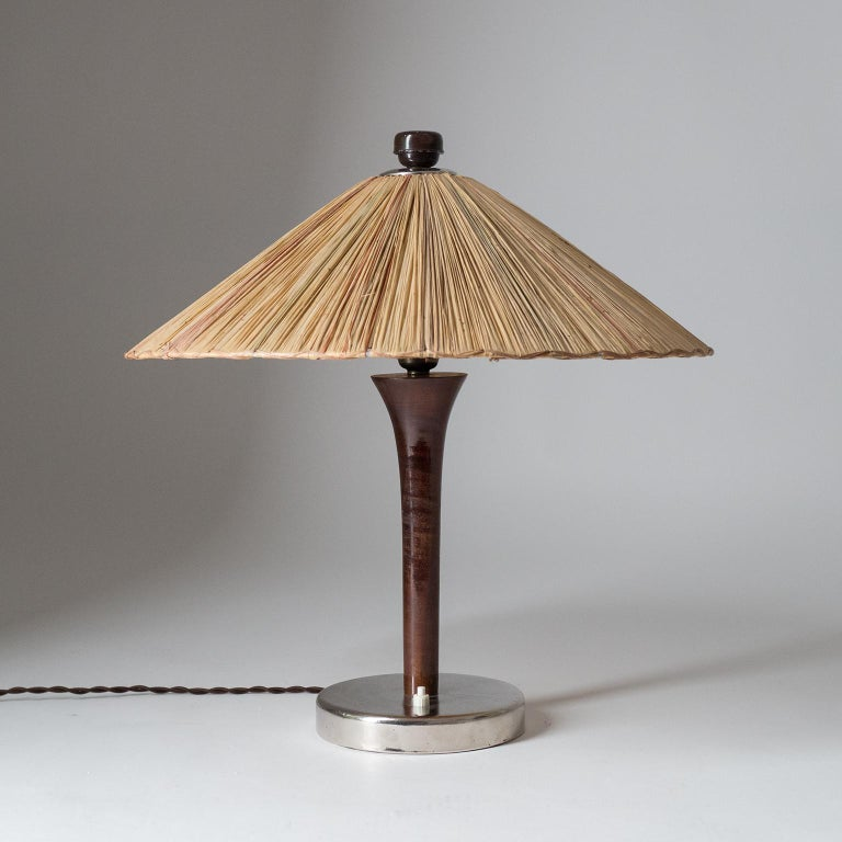 Rare 1930s table lamp with original straw shade. A weighted and chromed base holds a turned Tulip-shaped wooden stem and a large straw shade with different colored elements. Nice original condition with minor patinato the chrome and lacquered