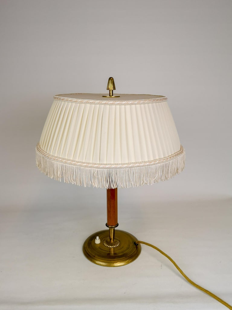 Art Deco table lamp brass and teak, Sweden, 1930s  Nice looking table lamp in Art Deco style. It made from Brass and Teak with an original fringe shade.   Good vintage condition.   Measures H 44 cm, D Shade 35 cm, D Foot 17 cm.