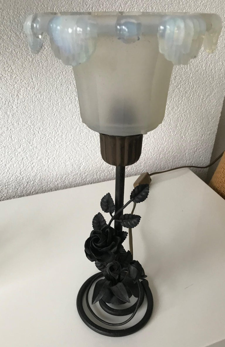Rare 1920s wrought iron table lamp with a René Lalique style shade.  With perfectly hand forged branches, leaves and roses at the base of this finest workmanship table lamp, it is as sturdy and stable as the day it was made. The stunning glass shade