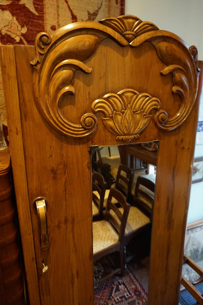Art Deco Armoire constructed from solid teak with a hand carved facade and steamed edges. Beautiful flowing golden grains of teak. Single piano hinge supporting solid door frame. Inside it houses two drawers and a hanging rack. Raised on a satin