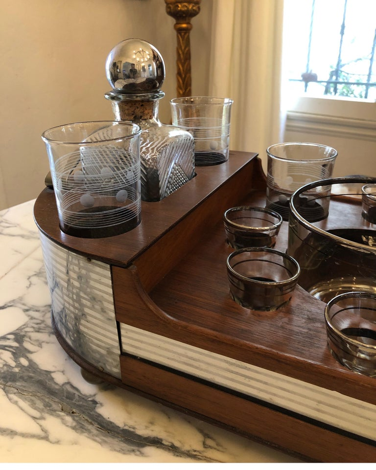 American, 1st half 20th century. Art Deco style chromed metal and wood portable bar or drinks set, the fitted tray having an oblong shape with rounded handles to each end and Inserts for bourbon decanter, scotch decanter, six shot glasses, six