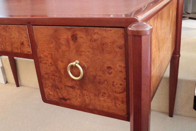 An Art Deco desk. Mahogany and birch burl with patinated bronze pulls  and leather top with gold tooling.