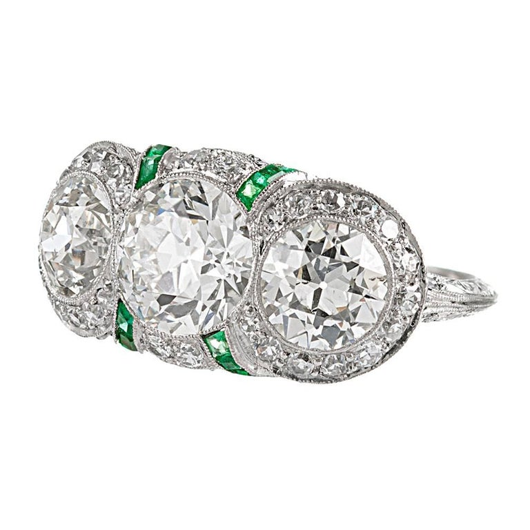 An exceptional creation, handmade in platinum and adorned with finery at every opportunity, this ring possesses a level of detail and design intricacy that is rarely seen in modern jewelry. The ring is centered upon three old European cut diamonds,