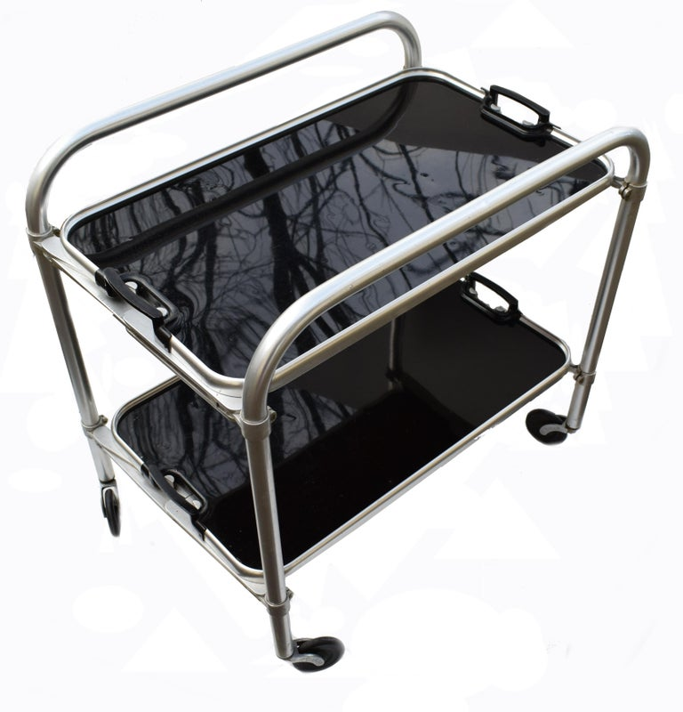Stylish English two-tier Art Deco aluminium and drinks hostess trolley bar cart. Dating to the 1930s and If glam is your thing then this is for you! In situ these carts look nothing less than superb. Can be used for serving or just displaying your