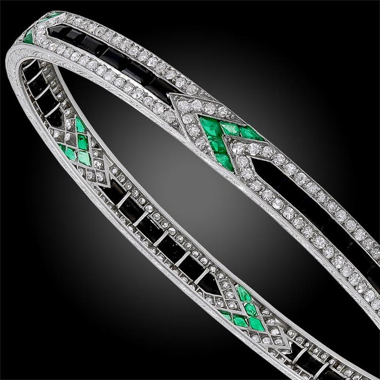 Emanating elegance and sophistication, comprising a 1920's platinum Van Cleef & Arpels bracelet of geometric design, finely set with several luminous diamonds, emeralds, and Onyx throughout. Signed Van Cleef & Arpels. Made in France