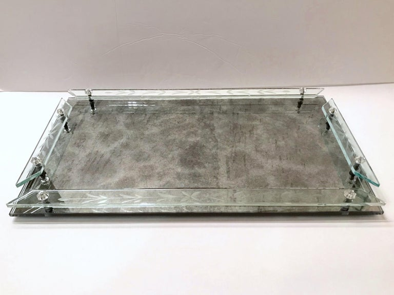 Art Deco era Venetian mirrored tray with smokey grey antique cast. The vanity tray is fitted with art glass gallery rails featuring elegant hand etched floral designs, and features glass rosette accents. Perfect for perfume bottles or as a barware