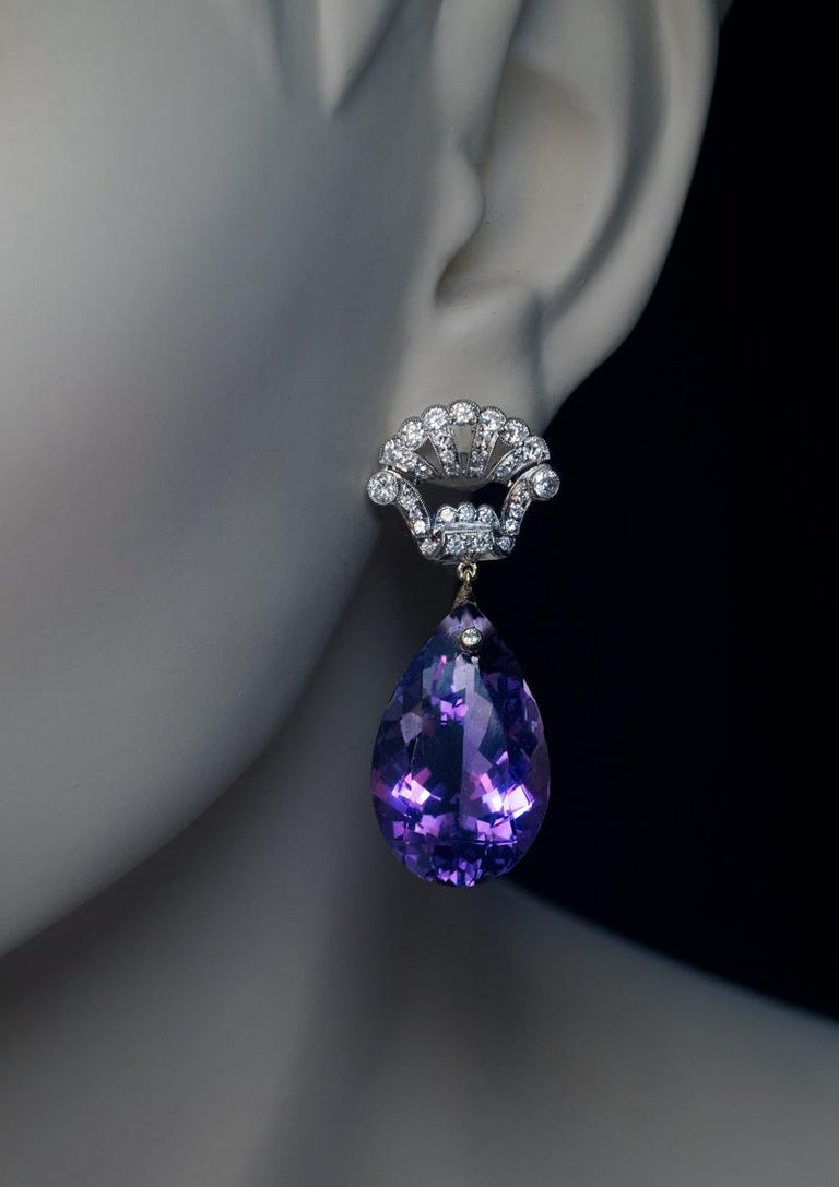 Circa 1935  This pair of vintage Art Deco era earrings features two large amethyst drops surmounted by crown motif platinum tops densely set with diamonds. Each amethyst drop is accented by a small old European cut diamond set in yellow gold