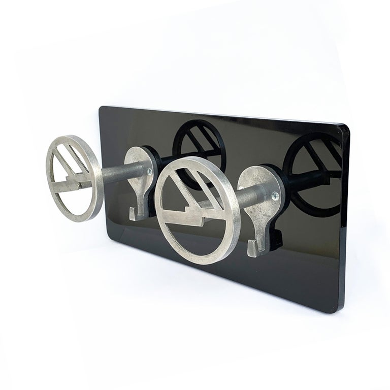 Detail of clothes hangers. The aluminium hooks are from the 1940s, mounted on a new shiny black plexiglas plate.