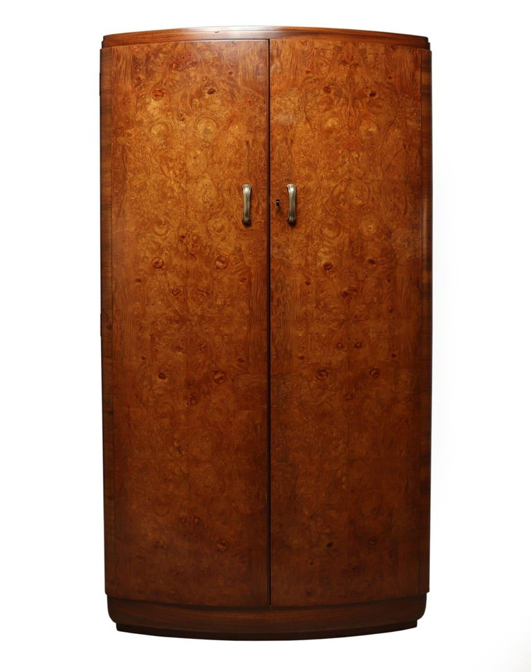 Art Deco walnut bow front gentleman wardrobe circa 1930 A fine quality English bow fronted burr walnut fitted gentleman's wardrobe having brass handles, the fitted interior has two drawers and a slide out trouser rail, the wardrobe has been fully