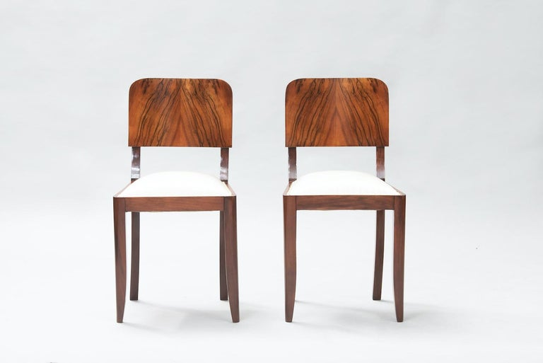 Set of six Art Deco walnut dining chairs, reupholstered in an ivory fabric.