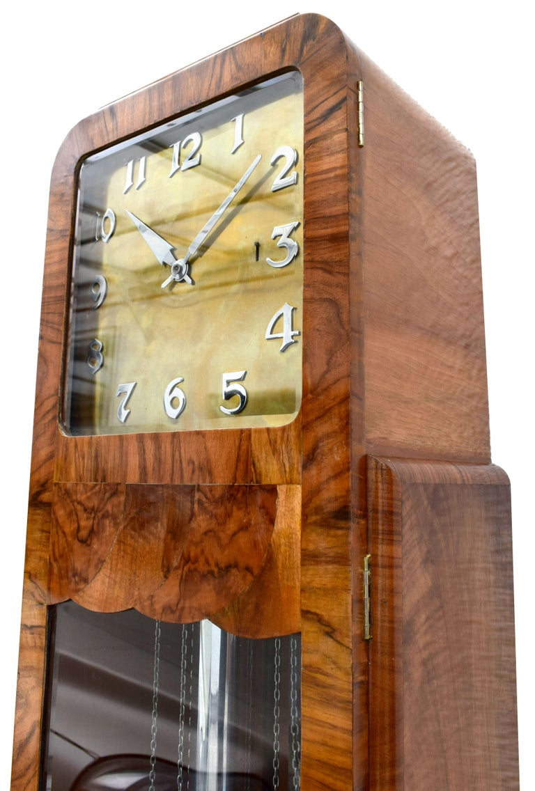 Magnificent Art Deco Grandfather clock dating to the 1930s, England. Extremely hard to source with such great styling. The craftsmanship to the case is spectacular, veneered in a mid tone walnut with beautiful detailing accentuating the shape, no