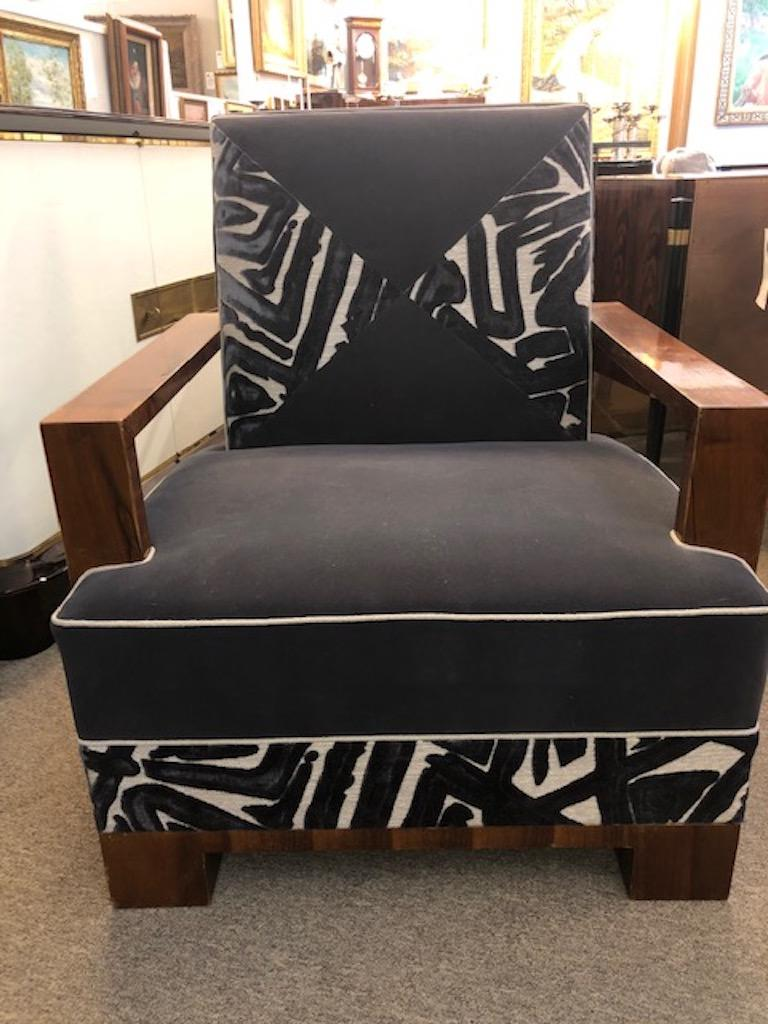The chair is made out of high quality walnut wood. Re-polished and re-upholstered in a graphite color velvety fabric. The chair has wide rectangular arm rests and four square legs, which are elevating the chair. Condition is excellent.