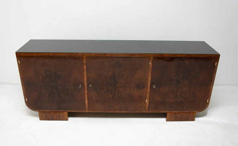This sideboard was made in Bohemia in the 1930s. It´s an example of Central European functionalism and is made of solid wood and veneered in walnut. It features a storage space divided to three parts and the top is covered with a black glass. The