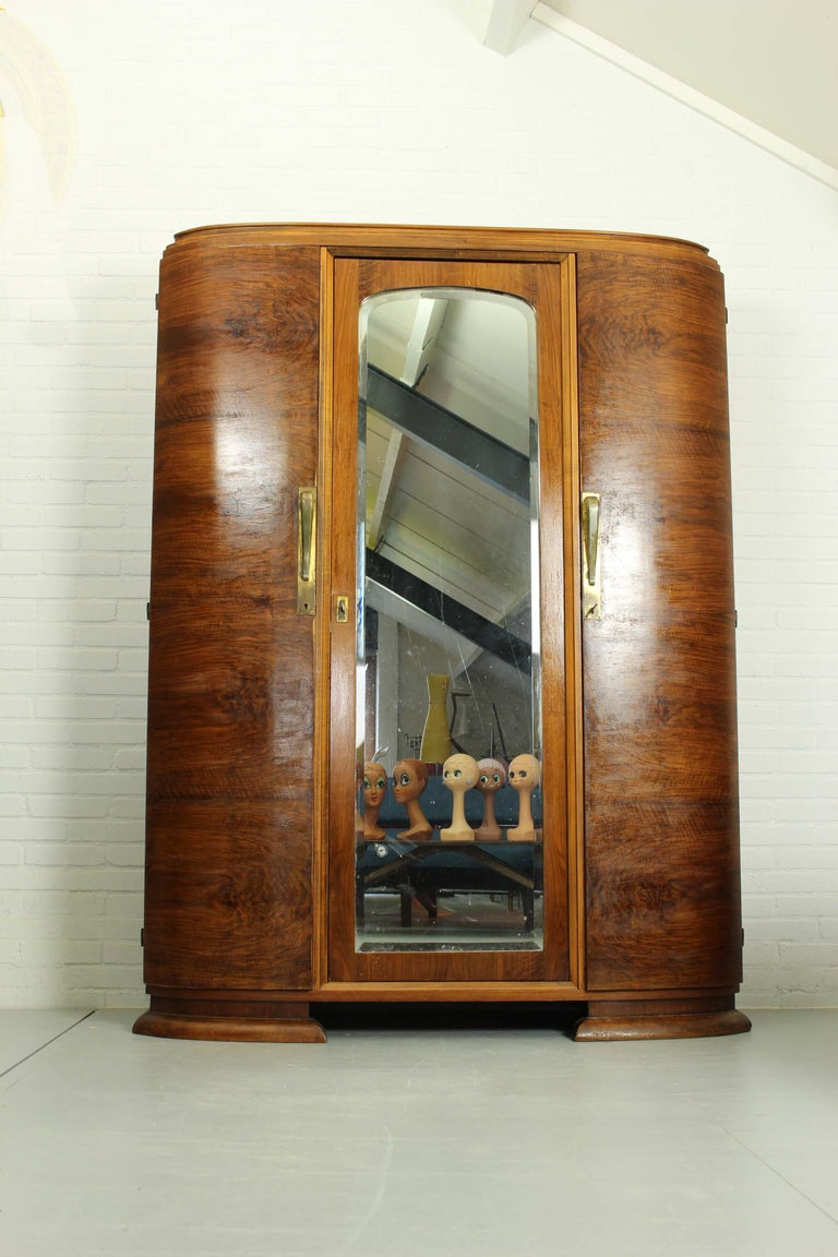 A fine quality, Art Deco, walnut cabinet produced by Georges Guerin in Paris in the 1920s. 3 Shaped walnut doors with beautiful handles on the outside and a drawer behind. Bevelled edge mirror on the middle door. In good vintage condition with wear