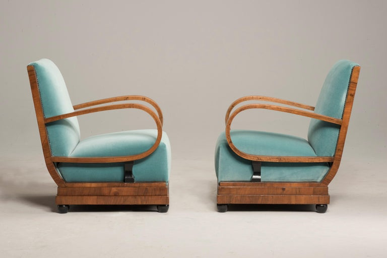 Art Deco armchairs and ottomans in light green velvet.   Pair of armchairs From 1930s period from France. Armchairs have walnut wood structure that can be appreciate on the rectangular back rest. Feet are black ebonized and have spherical shape.