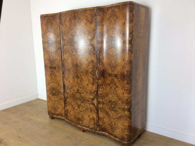 Art Deco serpentine wardrobe. Incredible Art Deco wardrobe of serpentine design with the most stunning figured walnut. Great design with exceptional quality. Measures: 192 cm H, 179 cm W, 55 cm D. British, circa 1928.