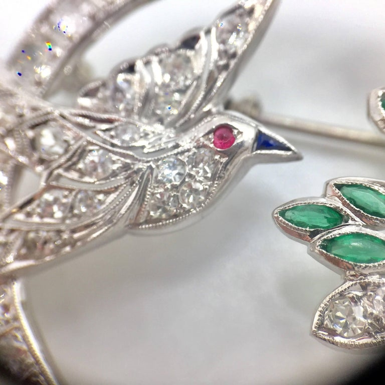Circa 1950's, this beautiful Art Deco -inspired detailed brooch is adorned with diamonds, emeralds, sapphires and a ruby. Perfect for an antique jewelry lover. This interesting piece can easily be converted to a pendant.