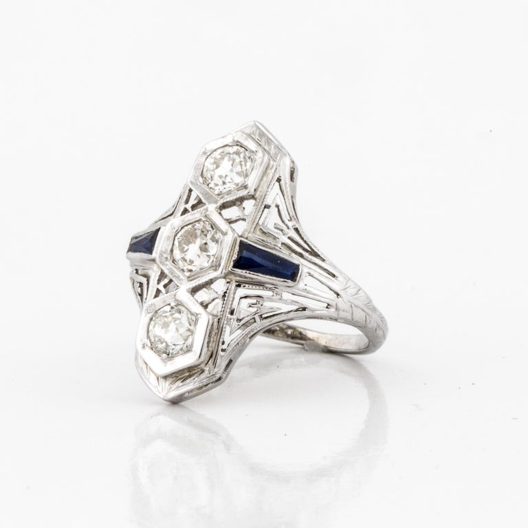 1930's 18K white gold diamond ring set with diamonds and synthetic sapphires.  There are three (3) Old European Cut diamonds with total carat weight of 0.75; they are I-J in color and VS in clarity.  The two side sapphires are synthetic which was