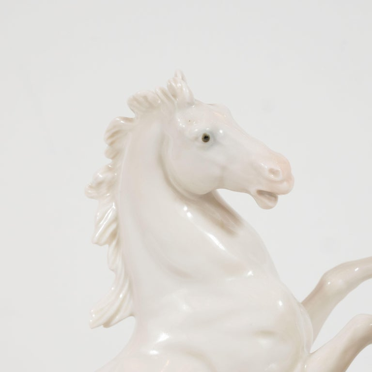 This stunning and dynamic white porcelain sculpture was realized by the esteemed artisan Karl Ens in East Germany, circa 1930. It depicts two galloping horses- a stallion and a mare- in white porcelain with gray-blue eyes, offering the only flash of