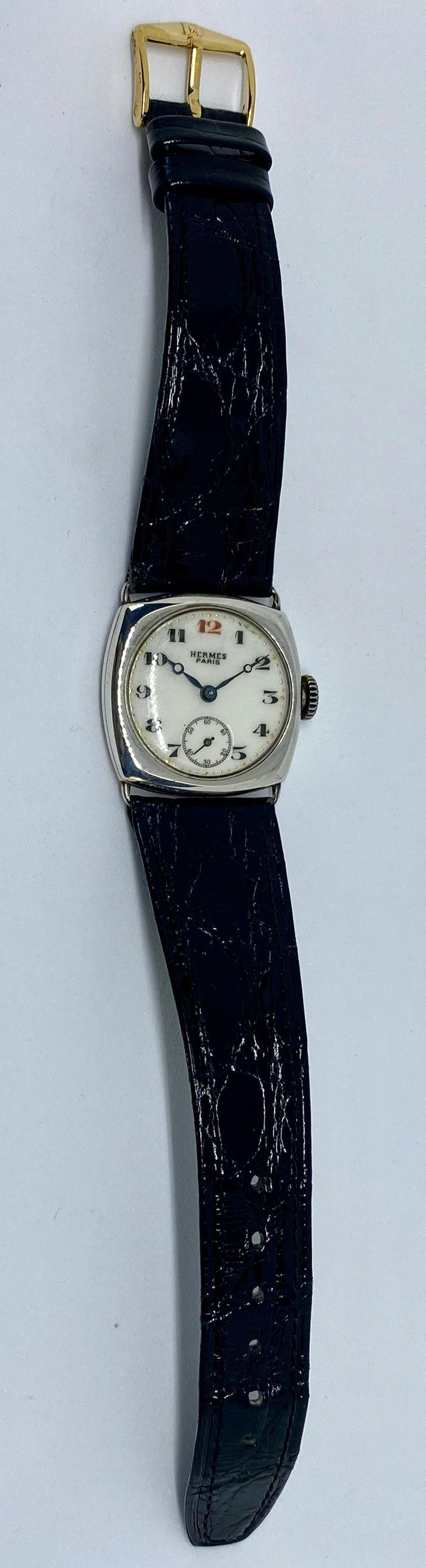 A vintage, entirely original, manual-wind wristwatch signed Hermes Paris.  Featuring a round, white porcelain face in a squared sterling silver case, with Breguet numerals in black (red at 12:00), Breguet (