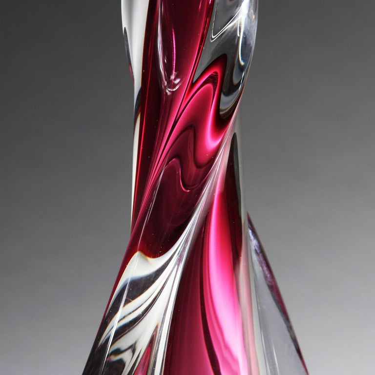 An art glass lamp with a twisting cerise body, by Vannes, France. Stamped to the base.  Currently wired for the UK. Please enquire for rewiring services.  Please note: Lampshade not included.