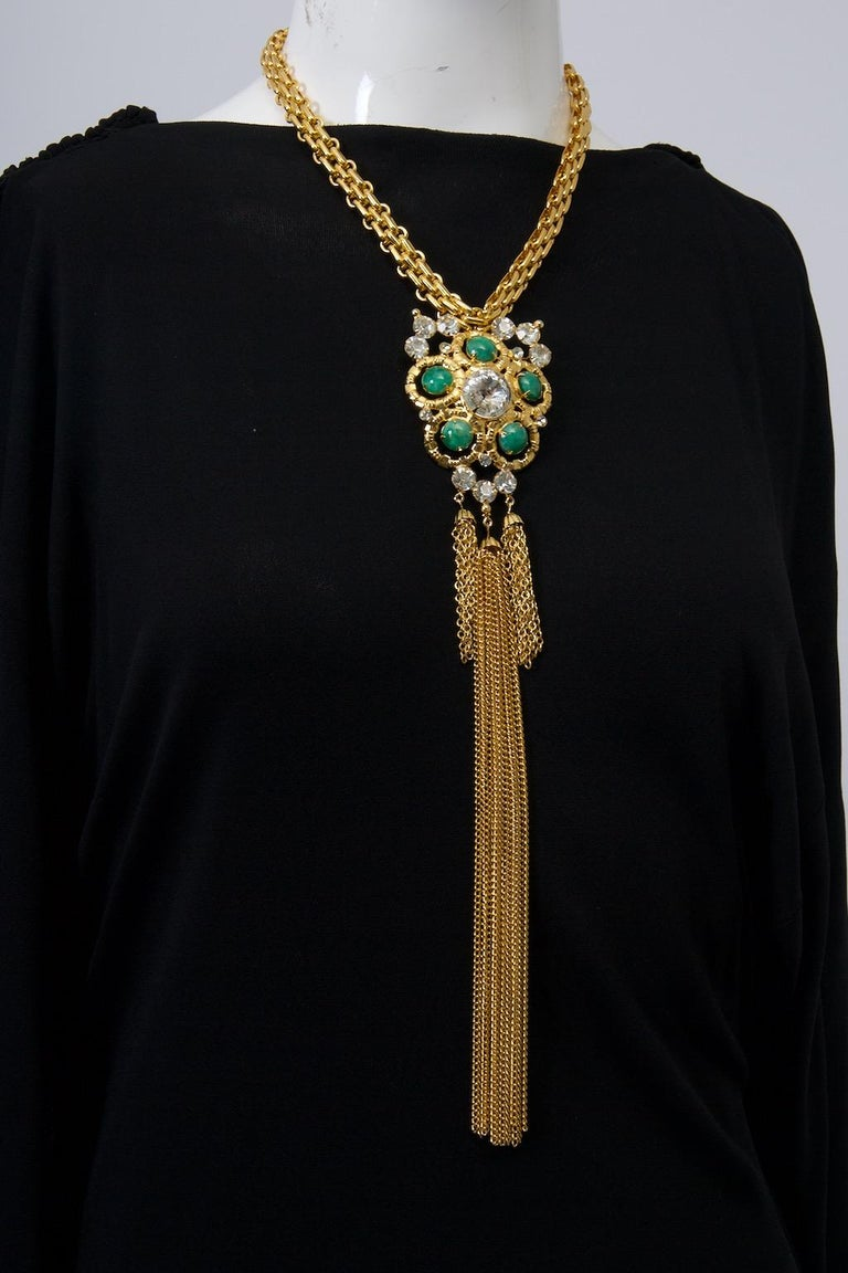An impressive piece by ART, founded in New York in the late 1940s as Mode-Art by Arthur Pepper, which can be worn as a necklace or brooch when the neck chain is detached. The central cinquefoil element features five green cabochon stones and clear