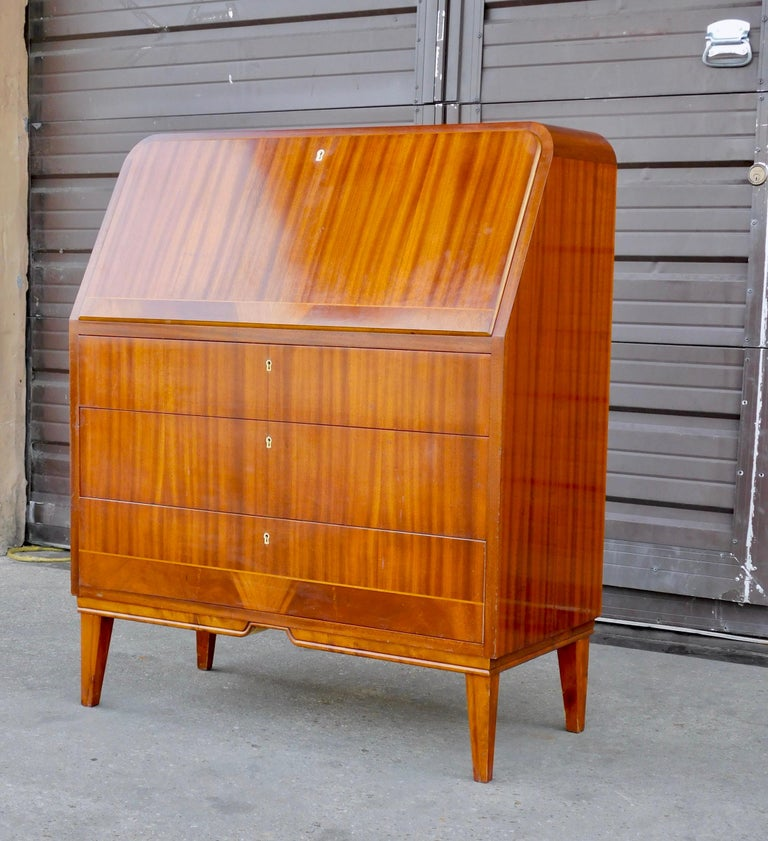 Swedish art moderne era secretaire desk rendered in striped mahogany. With interior in mahogany. Interior consists of slots and pullout / pull-out drawers. There is an area to conveniently store a lap top computer. The three lower drawers function